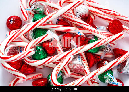 A pile pf red and white candy canes and colorful Hershey kisses for the holiday season. - Stock Image