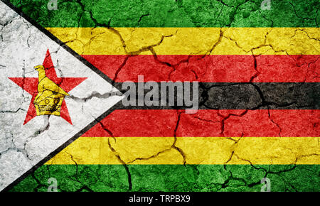 Republic of Zimbabwe flag on dry earth ground texture background - Stock Image