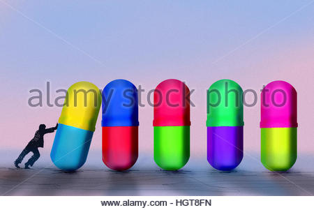 Man pushing large pills in domino effect - Stock Image