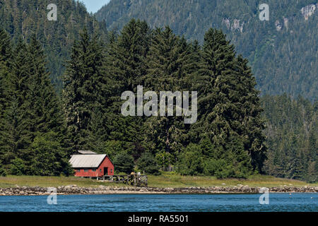 A red cottage along the Wrangell Narrowson Kupreanof Island across from Petersburg in southeast Alaska. - Stock Image