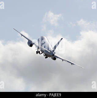 Sukhoi Superjet prototype taking-off in the flying-display during the Farnborough Airshow 2010 climbing towards cumulus clouds with undercarriage retr - Stock Image