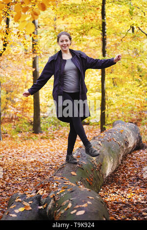 happy carefree young woman balancing on tree trunk in forest - enjoying active lifestyle in fall season - Stock Image