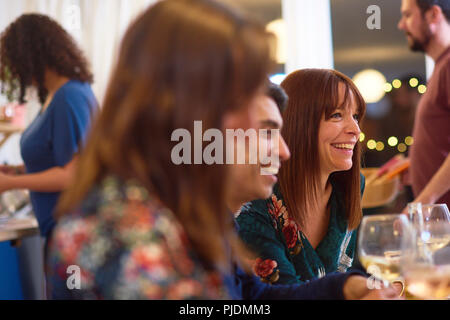 Friends laughing at dinner party - Stock Image