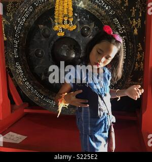 Young Asian girl taking a selfie  in a temple in Laos - Stock Image