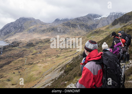 Hikers on lower slopes of Y Garn above Nant Ffrancon looking at view to Ogwen Valley in Snowdonia National Park Wales UK Britain - Stock Image