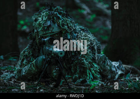 United States Army ranger sniper wearing ghillie suit. - Stock Image