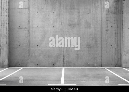 Several empty parking lots in an open garage with concrete wall - Stock Image