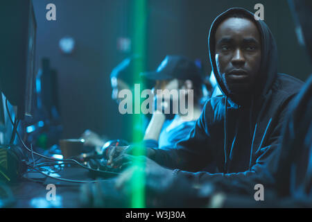 Tired young Black app developer in hoodie sitting at table and advising colleague while working on new app - Stock Image