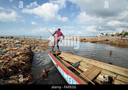 Man on boat in a rubbish dump in Kroo Bay, Freetown, Sierra Leone. - Stock Image