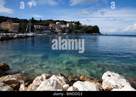 Rocks stretch into the clear blue sea - Stock Image