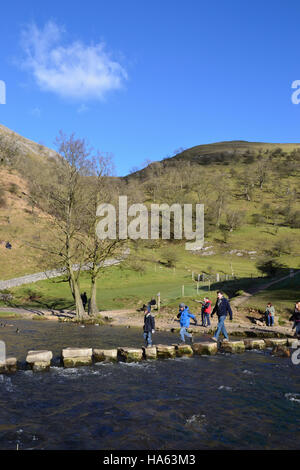 A family crossing the stepping stones at Dovedale in the Derbyshire Peak District. - Stock Image