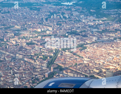 Plane landing in Turin, Italy, with city view below - Stock Image
