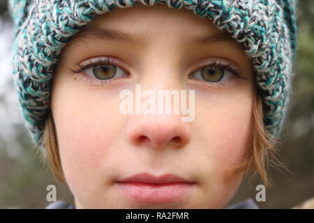 Closeup of a green eyed girl with a pensive stare wearing a winter hat - Stock Image