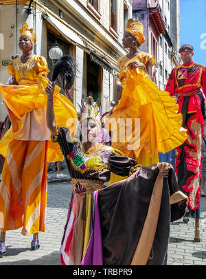 Colourfully dressed stilt walkers perform in one of the old streets in the Old Town of Havana, or Havana Vieja, Cuba, Caribbean - Stock Image