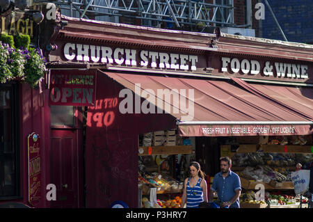 food wine and fruit for sale on stoke newington church street on a bright, sunny day in london under a red awning - Stock Image