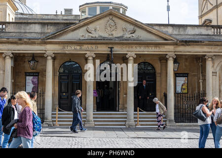 The exit from the Roman Baths in the city of Bath with ionic columns and pediment inscribed with King's and Queen's Baths - Stock Image