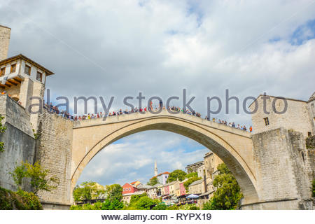 A local Bosnian prepares to jump off the Stari Most, the old bridge in Old Town Mostar, Bosnia and Herzegovina as tourists gather and watch from along - Stock Image