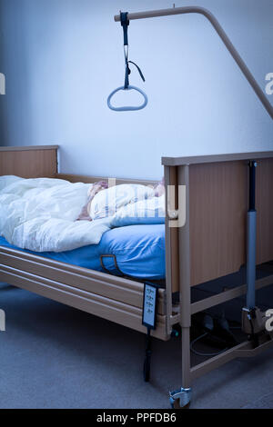 Dead person with extremly thin arms and joined hands in a nursing bed at home or in a hospice room, conept of death, blue filter effect - Stock Image