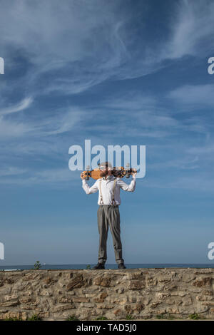 Man with longboard on his shoulders standing on a wall looking at distance - Stock Image