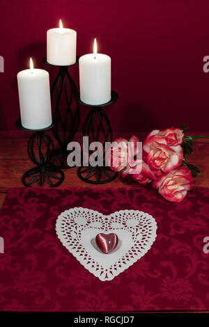 Heart shapped dollie and gemstone, three white candles in metal holoders and bouquet of orange and white roses on wooden table. - Stock Image