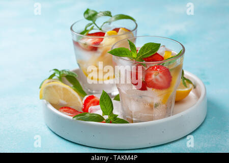 strawberry basil lemonade in a glass, fresh strawberries, basil on a blue background - Stock Image