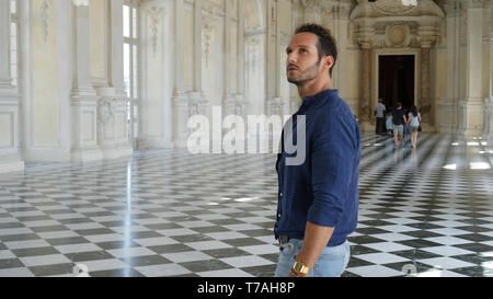 Handsome Man Looking Around Inside a Museum - Stock Image