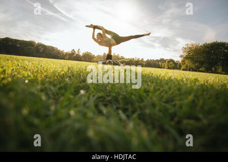 Fit young couple doing acroyoga on grass. Man and woman in park practising pair yoga poses. - Stock Image