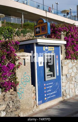 Standalone ATM built into a stone wall on the beach promenade, Benalmadena, Costa del sol, Spain - Stock Image