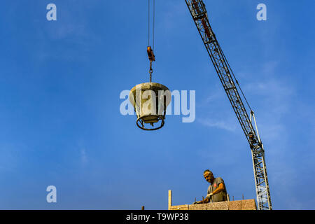 GARDA, LAKE GARDA, ITALY - SEPTEMBER 2018: Tower crane lowering a heavy steel bucket of concrete to a worker on a building site in the town of Garda o - Stock Image