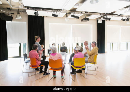 Active seniors clapping for instructor in circle in community center - Stock Image