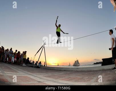 Male street performer balancing on tightrope while juggling, entertain crowds, Mallory Square Sunset Celebration, Key West, Florida Keys, Florida, USA - Stock Image