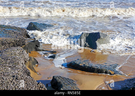 A close-up of waves on the shoreline at high tide on the Norfolk coast at Sea Palling, Norfolk, England, United Kingdom, Europe. - Stock Image