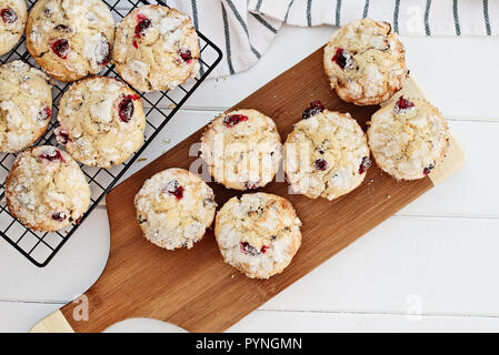 Fresh cranberry muffins cooling on a bakers rack and a wood cutting board over a rustic white table  background. Image shot from above with free space - Stock Image