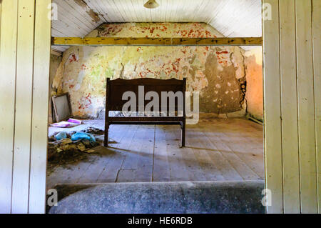 Bed left behind in an abandoned Irish cottage. - Stock Image