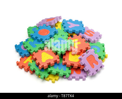 Pile of colorful foam alphabet puzzle pieces isolated on white - Stock Image