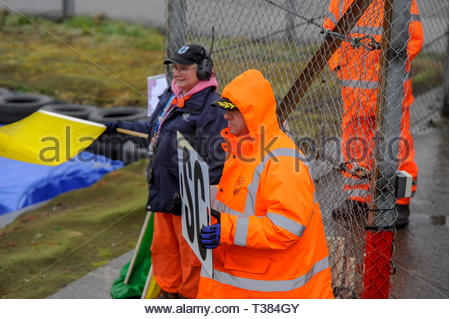 Dunfermline, Scotland, UK. 7th April, 2019.  Marshalls hold Safety Car board and flag during an incident in a Scottish Fiesta/Mini Cooper S Cup  race at Knockhill Circuit. During a wet and misty opening round of the Scottish Championship Car Racing season organised by the SMRC (Scottish Motor Racing Club) at Knockhill. Credit: Roger Gaisford/Alamy Live News - Stock Image