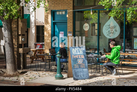 ASHEVILLE, NC, USA-10/17/18: Two people,a man and woman, sit separately at outside venue, using computers. - Stock Image