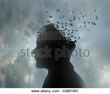 Man's head dissolving into flock of birds flying away - Stock Image