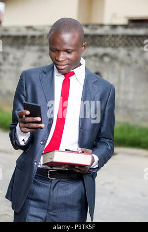 Young student holding a book in his left hand and manipulating a cell phone with the other hand - Stock Image