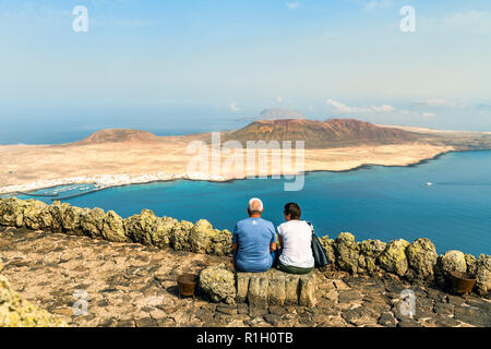 Two middle aged tourists sitting on a bench overlooking the small fishing and tourist village of Caleta del Sebo on the tiny island of La Graciosa nex - Stock Image