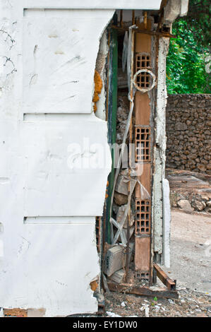 Part of a wall with damage, exposing underlying bricks - Stock Image