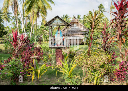 A Christian niche with a Virgin Mary statue in front of a Haus Tambaran, Korogo Village, Middle Sepik, Papua New Guinea - Stock Image