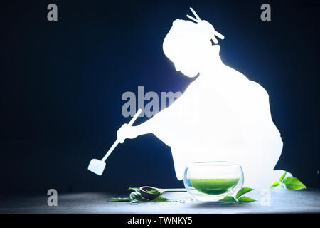 Tea ceremony with a shining woman silhouette brewing matcha tea. Double wall glass on the dark background with copy space - Stock Image