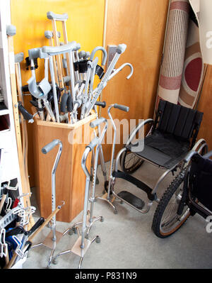 A box full of crutches and canes beside a wheelchair at a rehabilitation or physiotherapy clinic - Stock Image