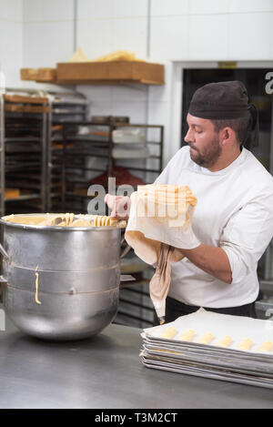 Pastry Chef with confectionary bag squeezing cream at pastry shop . - Stock Image