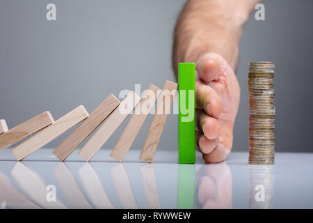 Human Finger Stopping Dominos From Falling With Stacked Coins On White Desk - Stock Image