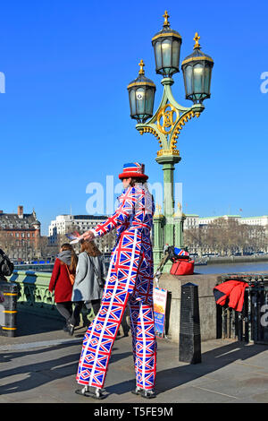 Man on stilts in clothes printed with Union Jack emblem in London tourism street scene giving leaflet advertising food restaurant London England UK - Stock Image