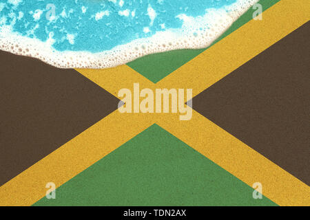 Sea wave on the sunny sandy beach with flag Jamaica. View from top on surf. - Stock Image