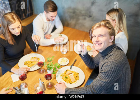Group of young people having lunch or dinner in restaurant or bistro - Stock Image