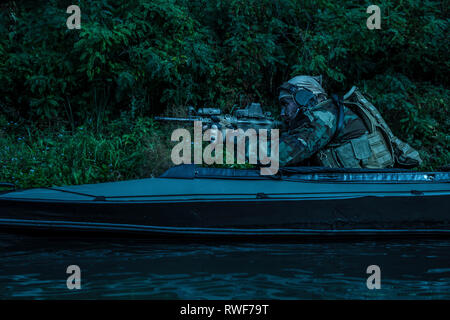 Special forces men paddling Army kayak across the river at twilight. - Stock Image